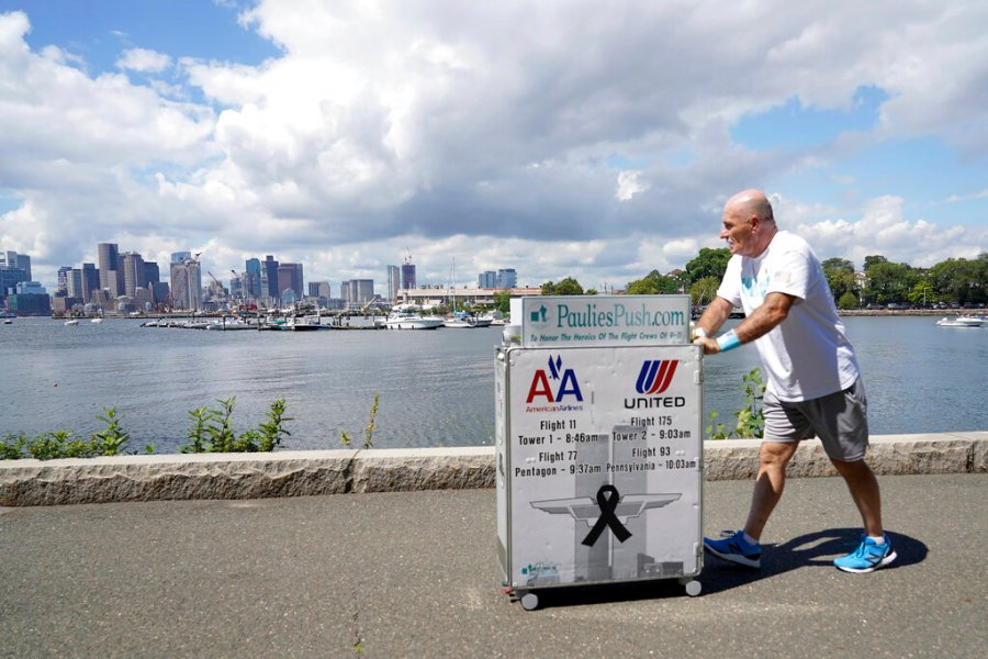 Paul Veneto pushes a beverage cart along Boston harbor, Saturday, Aug. 21, 2021. Veneto, a former flight attendant who lost several colleagues when United Flight 175 was flown into the World Trade Center on Sept. 11, 2001, is honoring his friends on the 20th anniversary of the terrorist attacks by pushing the beverage cart from Boston to ground zero in New York. (AP Photo/Mary Schwalm)