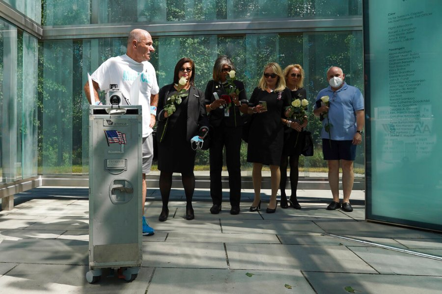 Paul Veneto, left, is joined by flight attendants as he stands with his beverage cart inside the 9/11 memorial at Logan Airport in Boston, Saturday, Aug. 21, 2021. Veneto, a former flight attendant who lost several colleagues when United Flight 175 was flown into the World Trade Center on Sept. 11, 2001, is honoring his friends on the 20th anniversary of the terrorist attacks by pushing the beverage cart from Boston to ground zero in New York. (AP Photo/Mary Schwalm)