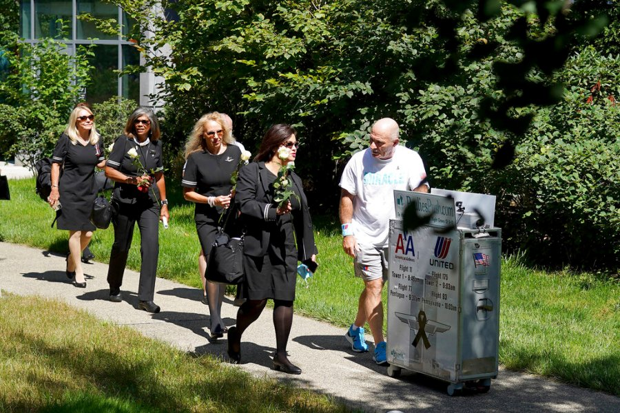 Paul Veneto, right, is joined by flight attendants as he pushes a beverage cart towards the 9/11 memorial at Logan Airport in Boston, Saturday, Aug. 21, 2021. Veneto, a former flight attendant who lost several colleagues when United Flight 175 was flown into the World Trade Center on Sept. 11, 2001, is honoring his friends on the 20th anniversary of the terrorist attacks by pushing the beverage cart from Boston to ground zero in New York. (AP Photo/Mary Schwalm)