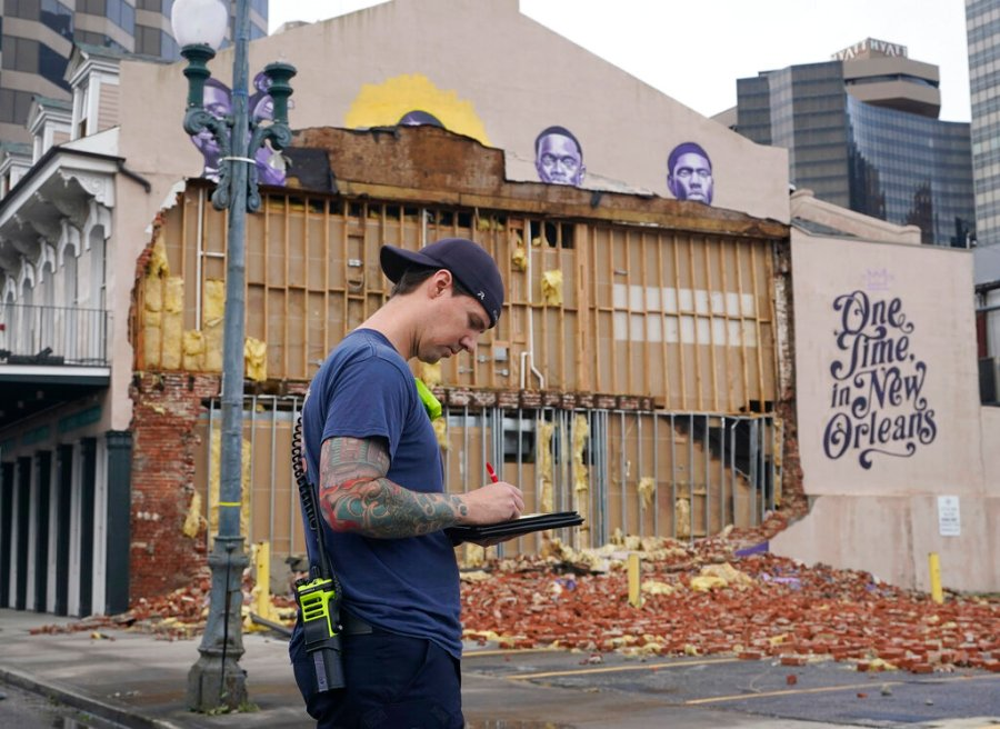 A New Orleans Firefighter assesses damages to downtown buildings resulting from the effects of Hurricane Ida, Monday, Aug. 30, 2021, in New Orleans, La. (AP Photo/Eric Gay)