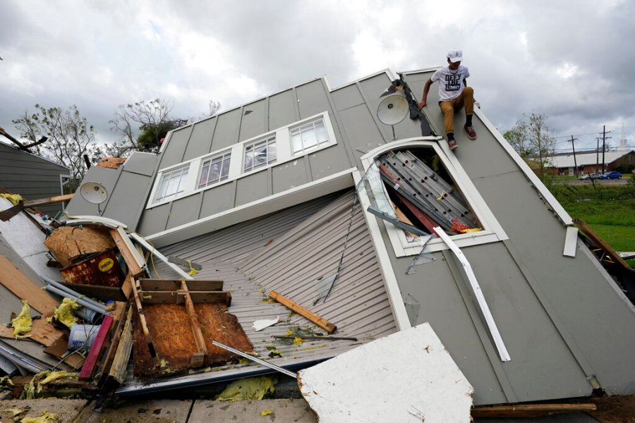 Jeremy Hodges climbs down the side of his family's destroyed storage unit in the aftermath of Hurricane Ida, Monday, Aug. 30, 2021, in Houma, La. (AP Photo/David J. Phillip)