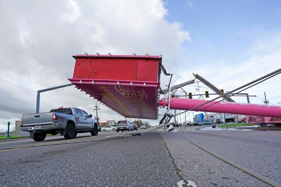 Vehicles maneuver around a fallen sign in the aftermath of Hurricane Ida, Monday, Aug. 30, 2021, in Houma, La. (AP Photo/David J. Phillip)
