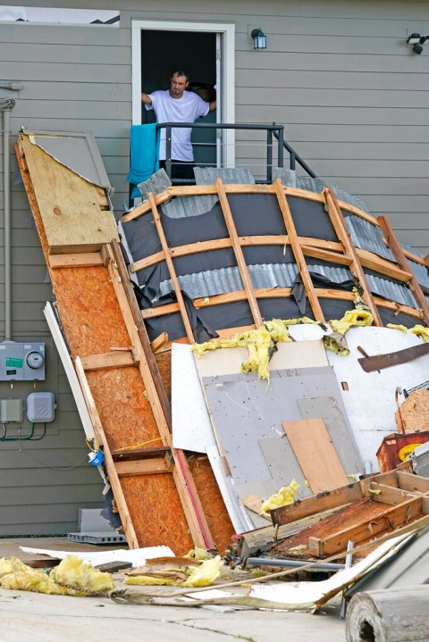 Ernie Bellinger looks out his second story door onto a damaged storage unit in the aftermath of Hurricane Ida, Monday, Aug. 30, 2021, in Houma, La. (AP Photo/David J. Phillip)