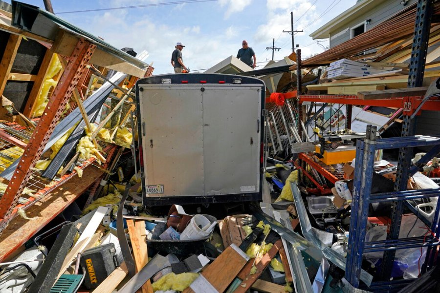 Jacob Hodges, right, and his brother Jeremy Hodges work to clear debris from their storage unit which was destroyed by Hurricane Ida, Monday, Aug. 30, 2021, in Houma, La. (AP Photo/David J. Phillip)