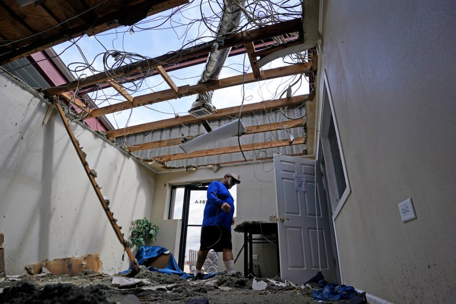 Rene Hebert walks through the family's destroyed offices as cleans up in the aftermath of Hurricane Ida, Monday, Aug. 30, 2021, in Houma, La. (AP Photo/David J. Phillip)
