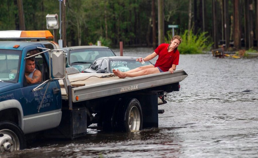 A woman rides on the back of a tow truck through floodwaters Monday, Aug. 30, 2021 in Shoreline Park community in Bay St. Louis. (Travis Long/The News & Observer via AP)