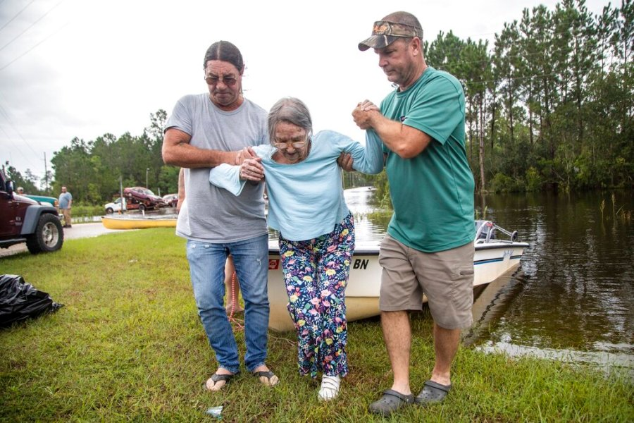 Stanley Delle, left, and Jeff Delle help 80-year-old Eileen Delle onto dry land Monday, Aug. 30, 2021 after floodwaters from Hurricane Ida surrounded her elevated home in the Shoreline Park community in Bay St. Louis. (Travis Long/The News & Observer via AP)