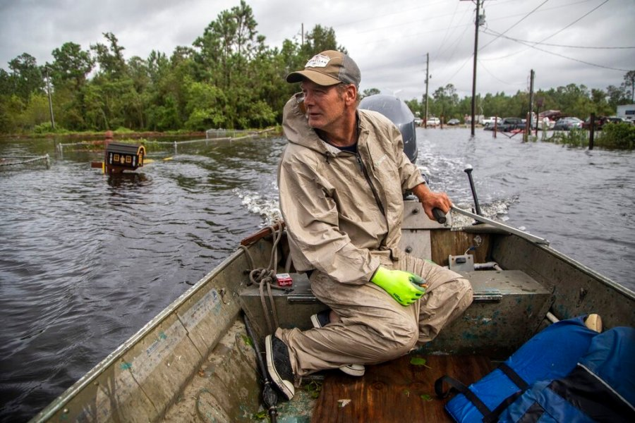 Eddie Gonzales pilots his boat through floodwaters in search of anyone who may need help in the Shoreline Park community in Bay St. Louis, Miss., on Monday, Aug. 30, 2021. (Travis Long/The News & Observer via AP)