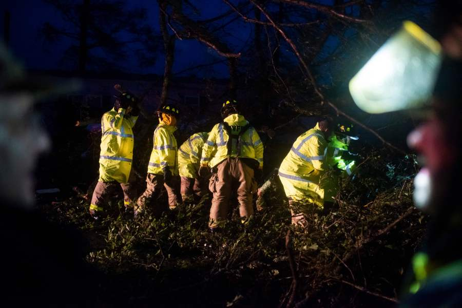 Montegut and Bourg firefighters cut through trees on the road in Bourg, Louisiana as Hurricane Ida passes on August 29, 2021. (Photo by MARK FELIX/AFP via Getty Images)