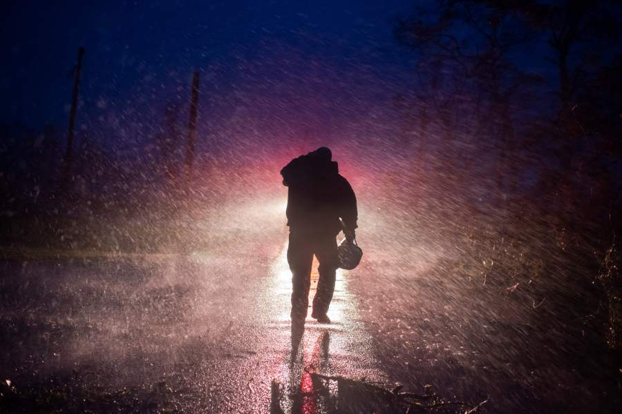 Montegut fire chief Toby Henry walks back to his fire truck in the rain as firefighters cut through trees on the road in Bourg, Louisiana as Hurricane Ida passes on August 29, 2021(Photo by MARK FELIX/AFP via Getty Images)