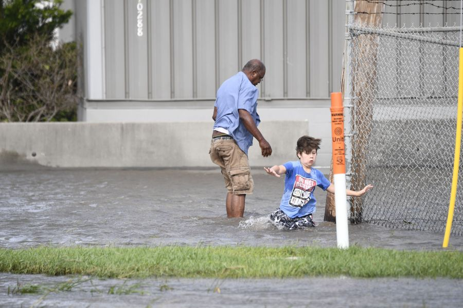 A man and his stepson walk through water in Saint Rose, Louisiana, on August 30, 2021 after Hurricane Ida made landfall.(Photo by PATRICK T. FALLON/AFP via Getty Images)