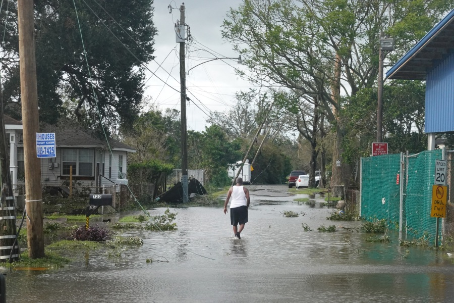 A man walks down a street flooded following Hurricane Ida on August 30, 2021 in Kenner, Louisiana. Ida made landfall yesterday as a category 4 storm southwest of New Orleans. (Photo by Scott Olson/Getty Images)