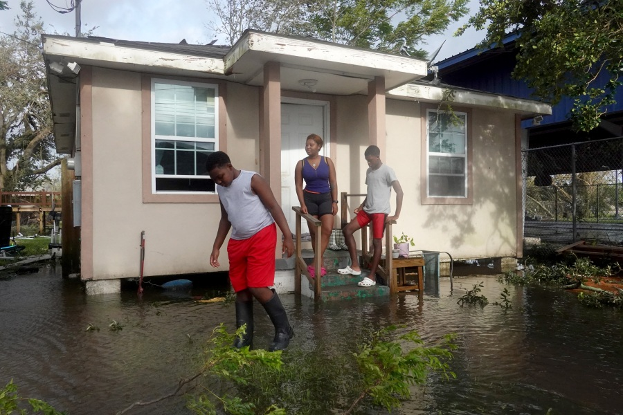 Michelle Washington and her sons Kendrick (R) and Kayden check out damage to their home in the aftermath of Hurricane Ida. (Photo by Scott Olson/Getty Images)