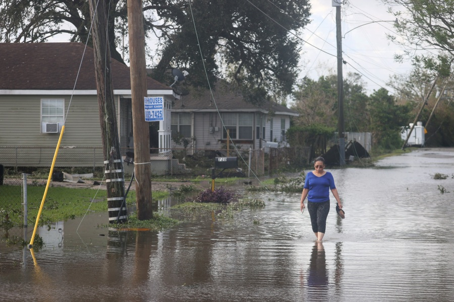 Angelina Coxum walks down a flooded street to check on a relatives home after Hurricane Ida passed through. (Photo by Scott Olson/Getty Images)