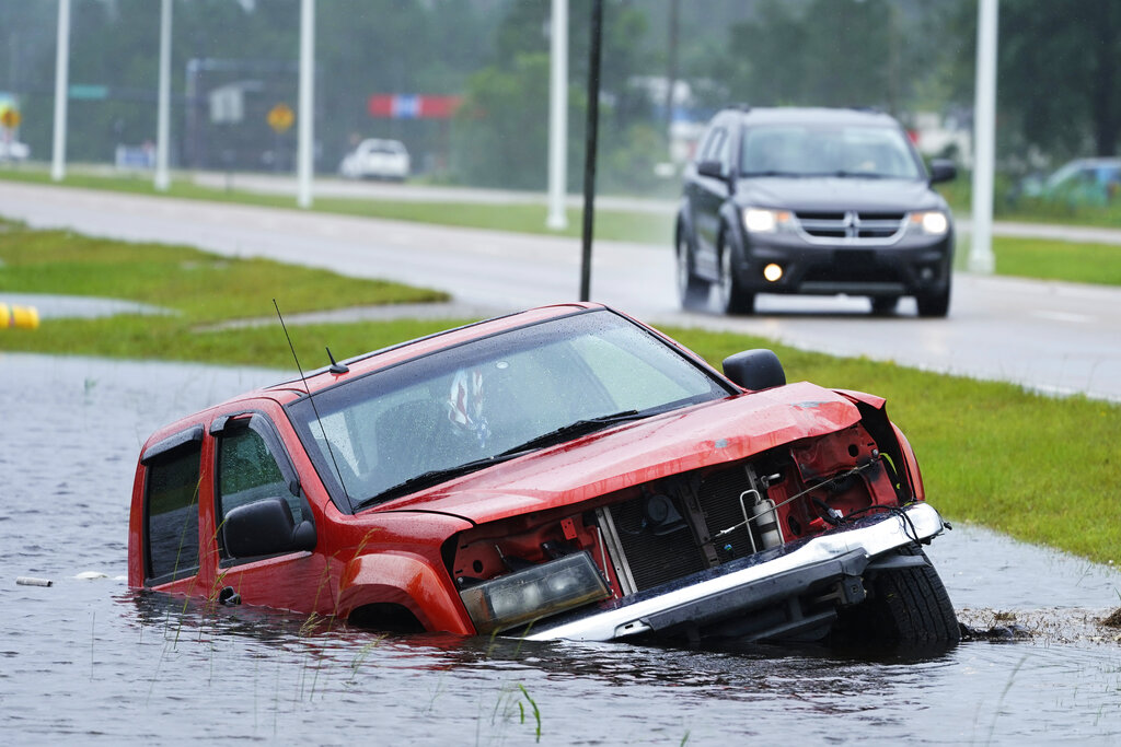 An abandoned vehicle is half submerged in a ditch next to a near flooded highway as the outer bands of Hurricane Ida arrive Sunday, Aug. 29, 2021, in Bay Saint Louis, Miss. (AP Photo/Steve Helber)