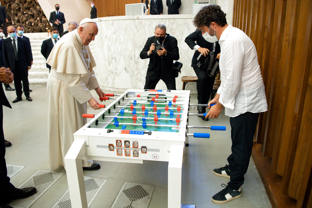 Pope Francis plays with Natale Tonini, president of Sport Toscana Calcio Balilla association, at the end of the weekly general audience, Wednesday, Aug.18. 2021. Francis played a round on the table that was presented to him by representatives of the association that created a special foosball table designed to be inclusive, for people with physical disabilities, to encourage their participation in sport. (Vatican Media via AP)