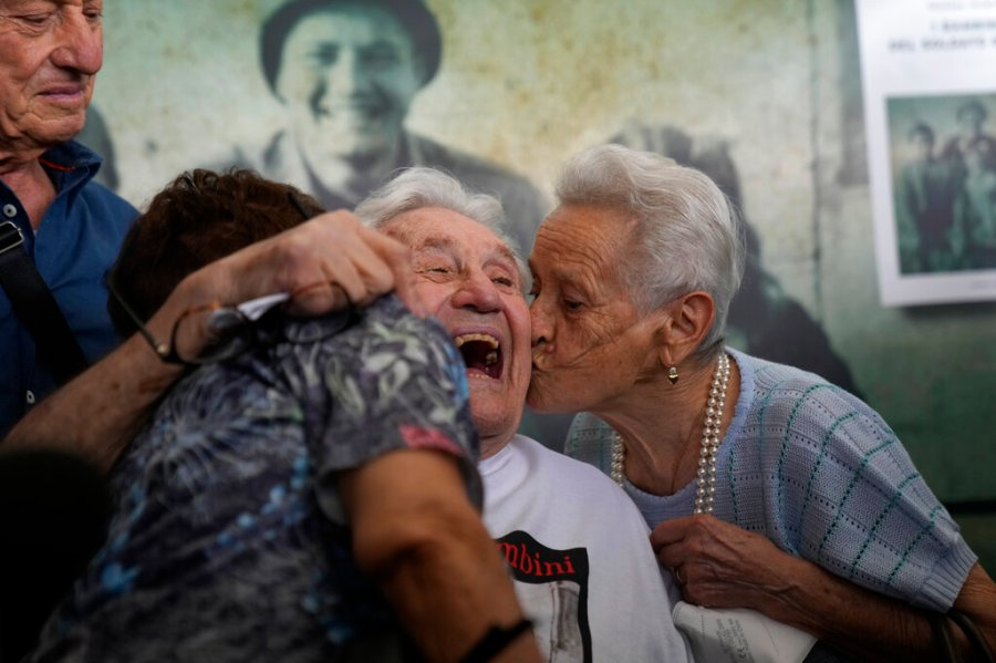 A 97 year old retired American soldier Martin Adler, center, receives a kiss by Mafalda, right, and Giuliana Naldi that he saved during a WWII, at Bologna's airport, Italy, Monday, Aug. 23, 2021. For more than seven decades, Martin Adler treasured a back-and-white photo of himself as a young soldier with a broad smile with three impeccably dressed Italian children he is credited with saving as the Nazis retreated northward in 1944. The 97-year-old World War II veteran met the three siblings -- now octogenarians themselves -- in person for the first time on Monday, eight months after a video reunion.  (AP Photo/Antonio Calanni)