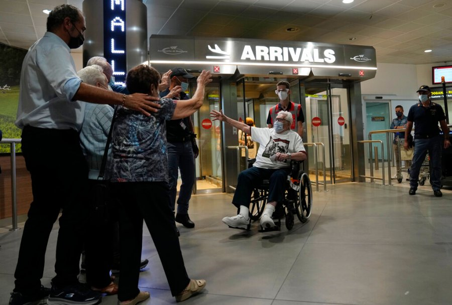 A 97 year old retired American soldier Martin Adler, right, is welcomed upon his arrival by Giulio Mafalda Giuliana Naldi that he saved during a WWII at Bologna's airport, Italy, Monday, Aug. 23, 2021. For more than seven decades, Martin Adler treasured a back-and-white photo of himself as a young soldier with a broad smile with three impeccably dressed Italian children he is credited with saving as the Nazis retreated northward in 1944. The 97-year-old World War II veteran met the three siblings -- now octogenarians themselves -- in person for the first time on Monday, eight months after a video reunion. (AP Photo/Antonio Calanni)