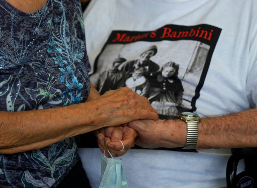 A 97 year old retired American soldier Martin Adler holds Giuliana Naldi's hand that he saved during a WWII, at Bologna's airport, Italy, Monday, Aug. 23, 2021. For more than seven decades, Martin Adler treasured a back-and-white photo of himself as a young soldier with a broad smile with three impeccably dressed Italian children he is credited with saving as the Nazis retreated northward in 1944.  (AP Photo/Antonio Calanni)