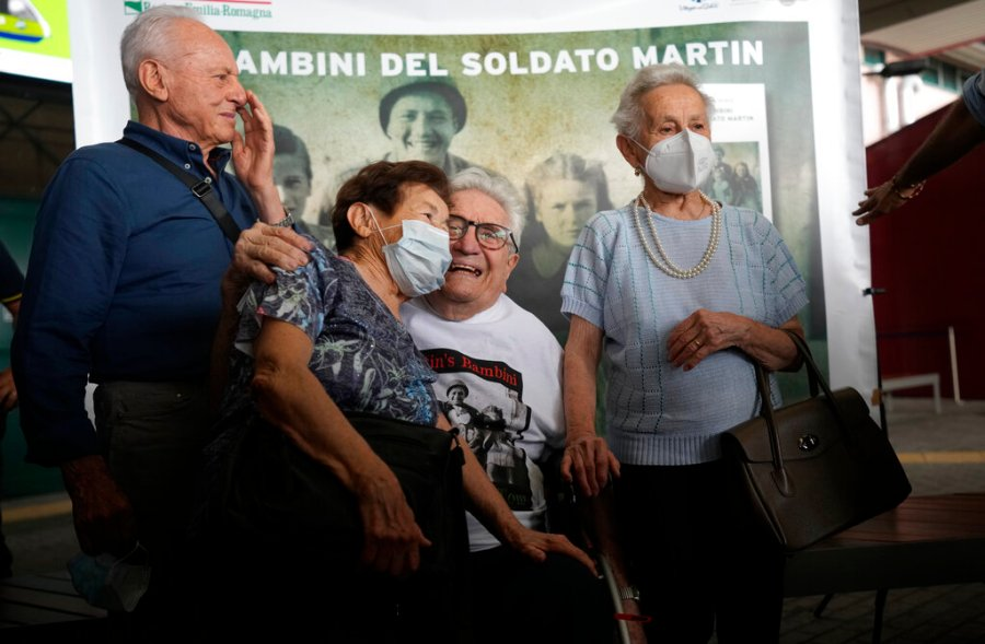 A 97 year old retired American soldier Martin Adler poses with Giulio, left, Mafalda, right, and Giuliana Naldi that he saved during a WWII at Bologna's airport, Italy, Monday, Aug. 23, 2021. For more than seven decades, Martin Adler treasured a back-and-white photo of himself as a young soldier with a broad smile with three impeccably dressed Italian children he is credited with saving as the Nazis retreated northward in 1944. The World War II veteran met the three siblings -- now octogenarians themselves -- in person for the first time on Monday, eight months after a video reunion.  (AP Photo/Antonio Calanni)