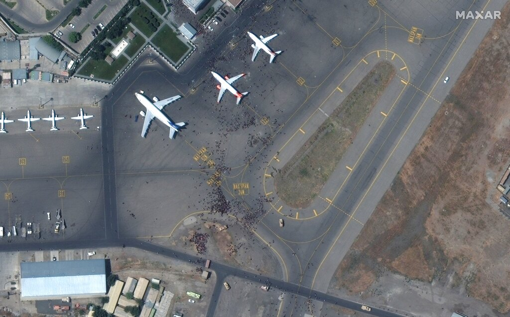 A satellite photo from Maxar Technologies shows swarms of people on the tarmac at Kabul International Airport, also known as Hamid Karzai International Airport, Monday Aug. 16, 2021. Afghans rushed onto the tarmac of the capital's airport on Monday as thousands tried to flee the country after the Taliban seized power with stunning speed. Some clung to the side of a U.S. military transport plane before takeoff, in a widely shared video that captured the sense of desperation as America's 20-year war comes to a chaotic end. (Satellite image ©2021 Maxar Technologies via AP)