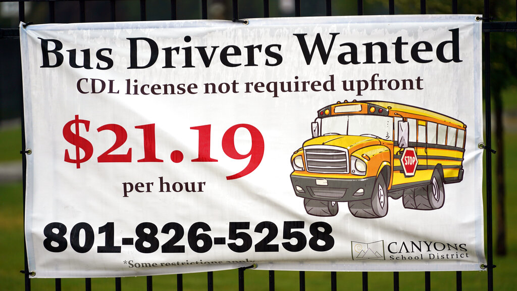 """A """"Bus Drivers Wanted"""" sign in Sandy, Utah. A shortage of bus drivers is complicating the start of a new school year already facing a surge in COVID-19 cases and conflicts over whether masks should be required in school buildings. (AP Photo/Rick Bowmer)"""