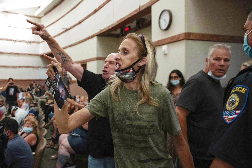 Protesters against a COVID-19 mandate gesture as they are escorted out of the Clark County School Board meeting at the Clark County Government Center, on Thursday, Aug. 12, 2021, in Las Vegas. (Bizuayehu Tesfaye/Las Vegas Review-Journal via AP)