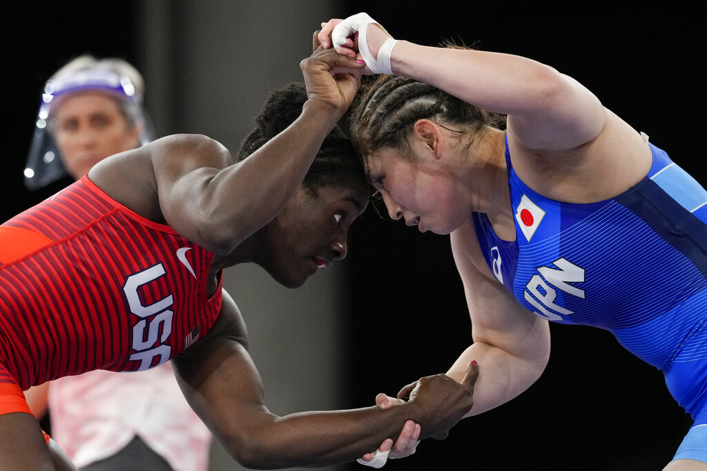 The United States' Tamyra Marianna Stock Mensah, left, and Japan's Sara Dosho compete during the women's 68kg freestyle wrestling match at the 2020 Summer Olympics in Chiba, Japan. Tokyo Olympians are exercising extraordinary discipline against the coronavirus. They are sealed off in a sanitary bubble that has made competition possible but is also squeezing a lot of fun from their Olympic experience. (AP Photo/Aaron Favila, File)