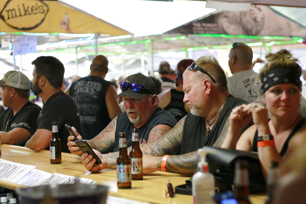 People congregate without masks at One-Eyed Jack's Saloon during the 80th annual Sturgis Motorcycle Rally in 2020. The annual rally refused to take 2020 off despite the threat of the coronavirus pandemic, a decision blamed for leading to a late-summer spike in cases across the Midwest. And it's about to roar right back this year, kicking off Friday, Aug. 6, 2021 with crowds expecting to be significantly larger even as the delta variant is rising. (AP Photo/Stephen Groves, File)