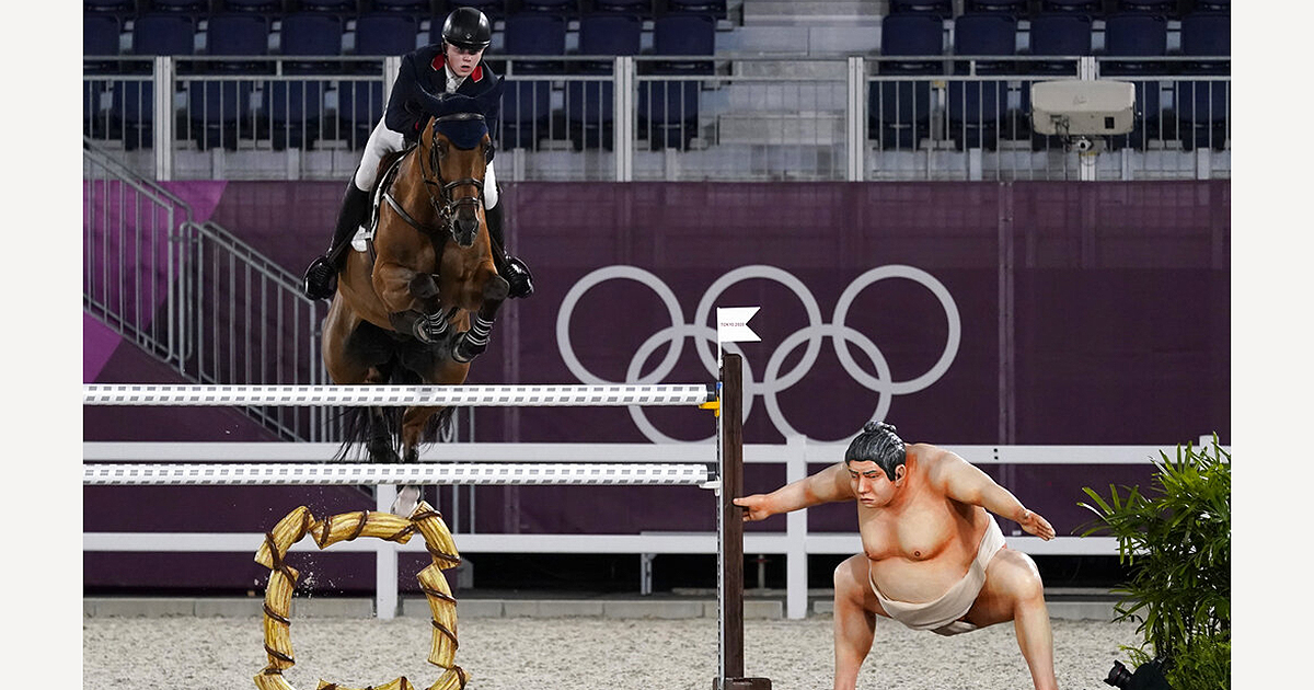 Britain's Harry Charles, riding Romeo 88, competes during the equestrian jumping individual qualifying at Equestrian Park in Tokyo next to the statue. (AP Photo/Carolyn Kaster)
