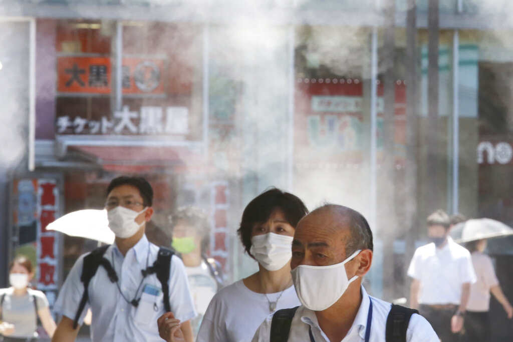 People wearing face masks to protect against the spread of the coronavirus walk under a water mist in Tokyo Thursday, Aug. 5, 2021. New cases surge in Tokyo to record levels during the Olympic Games. (AP Photo/Koji Sasahara)