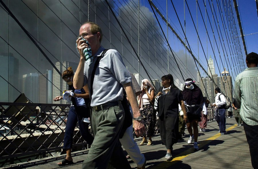 People walk over New York's Brooklyn Bridge from Manhattan to Brooklyn following the collapse of both World Trade Center towers on Sept. 11, 2001. (AP Photo/Mark Lennihan)