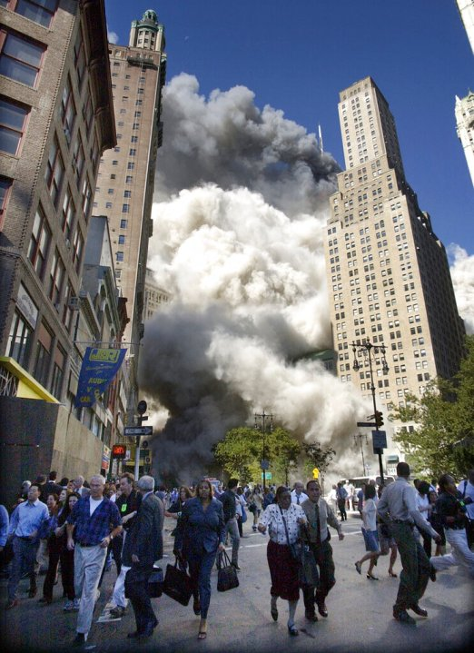 People flee the falling South Tower of the World Trade Center on Tuesday, Sept. 11, 2001. (AP Photo/Amy Sancetta)
