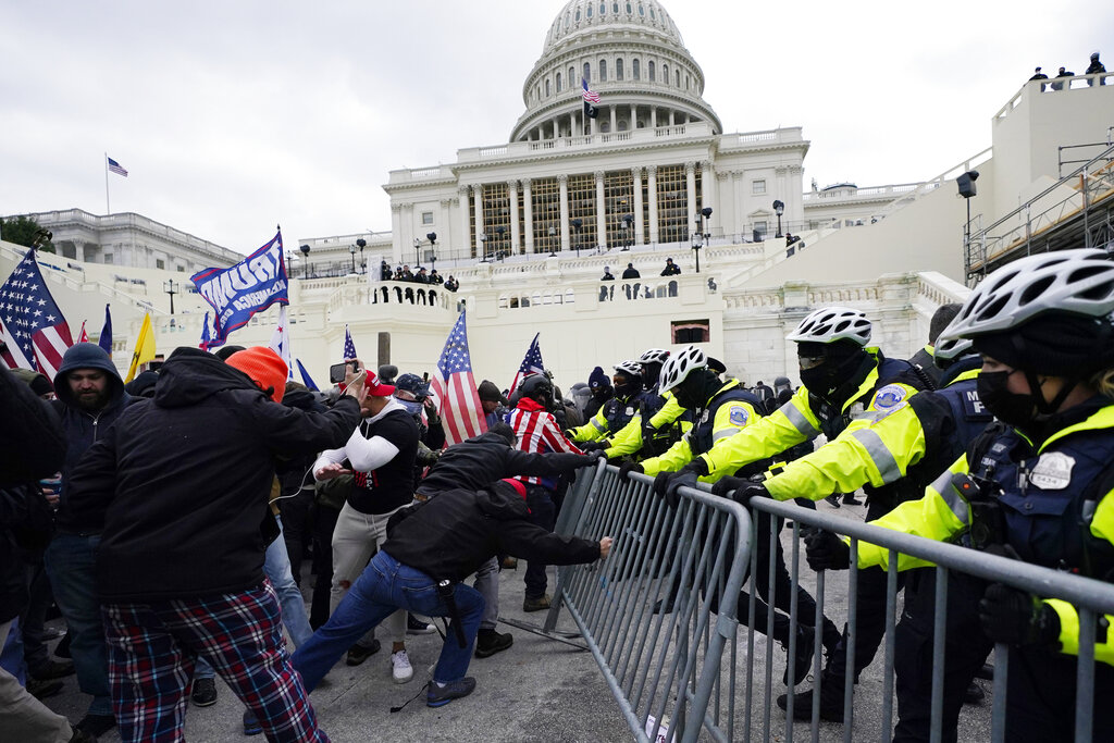 Supporters loyal to then-President Donald Trump, try to break through a police barrier at the Capitol in Washington. (AP Photo/Julio Cortez)
