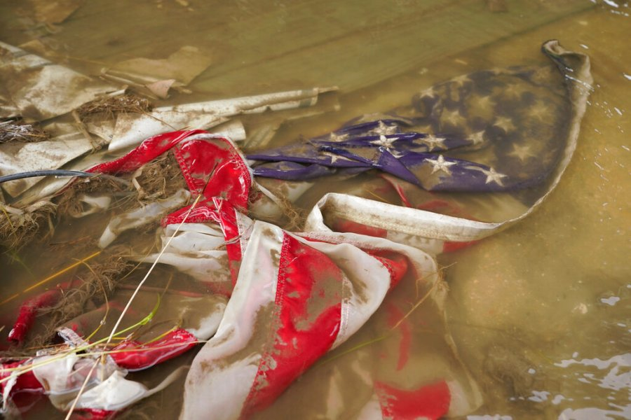 An American flag floats in a puddle of flood water in Myrtle Grove, La. (AP Photo/Steve Helber)