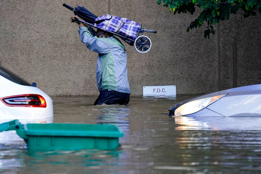 A person walks in floodwaters in Philadelphia in the aftermath of downpours and high winds from the remnants of Hurricane Ida that hit the area. (AP Photo/Matt Rourke)