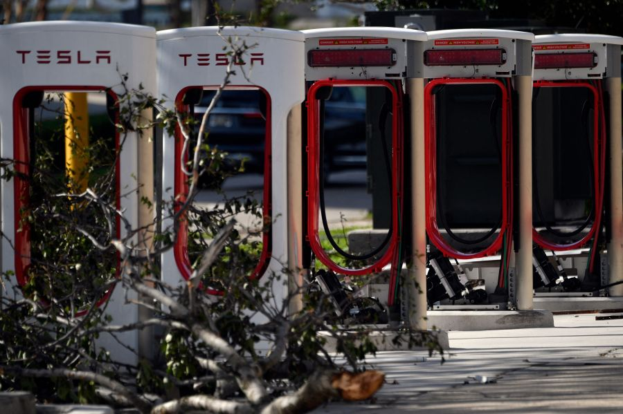 Fallen tree branches are seen on Tesla chargers after neighborhoods were flooded in New Orleans. (Photo by PATRICK T. FALLON/AFP via Getty Images)
