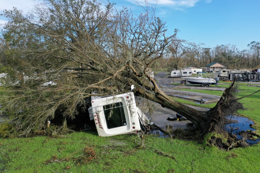 An flipped over RV sits under an uprooted tree in an RV park in Paradis, Louisiana. (Photo by Scott Olson/Getty Images)