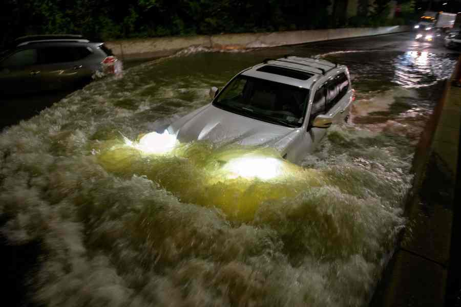 A motorist drives a car through a flooded expressway in Brooklyn, New York early on September 2, 2021, as flash flooding and record-breaking rainfall brought by the remnants of Storm Ida swept through the area. (Photo by ED JONES/AFP via Getty Images)