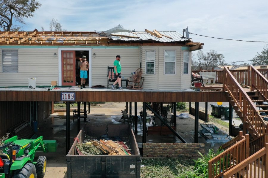 People walk across the deck of a home severely damaged by Hurricane Ida in Montegut, Louisiana. (Photo by Scott Olson/Getty Images)