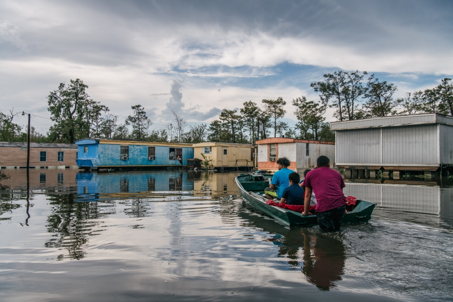 """The Maldonado family travel by boat to their home after it flooded during Hurricane Ida in Barataria, Louisiana. """"I've lost everything in my trailer because of the hurricane. I've lost everything, my family has lost everything and we're now trying to find help. We all live in this area and now its all gone,"""" said Fusto Maldonado when asked about the storm's effect. Power is out throughout New Orleans and the surrounding area. Ida made landfall as a Category 4 hurricane on August 29 in Louisiana and brought flooding and wind damage along the Gulf Coast.  (Photo by Brandon Bell/Getty Images)"""