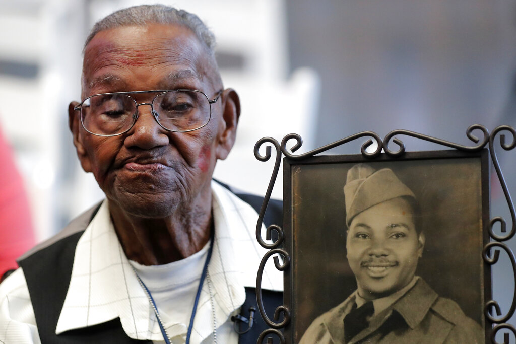 World War II veteran Lawrence Brooks holds a photo of him taken in 1943 in 2019. Brooks celebrated his 112th birthday, Sunday, Sept. 12, 2021 with a drive-by party at his New Orleans home hosted by the National War War II Museum. Drafted in 1940, Brooks was a private in the Army's mostly Black 91st Engineer Battalion. (AP Photo/Gerald Herbert, File)