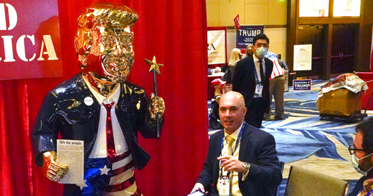 Look Ahead America sponsor Matt Braynard, center, talks to conference attendees at his booth in the merchandise show with a statue of former president Donald Trump at the Conservative Political Action Conference (CPAC) in Orlando, Fla. (AP Photo/John Raoux, File)