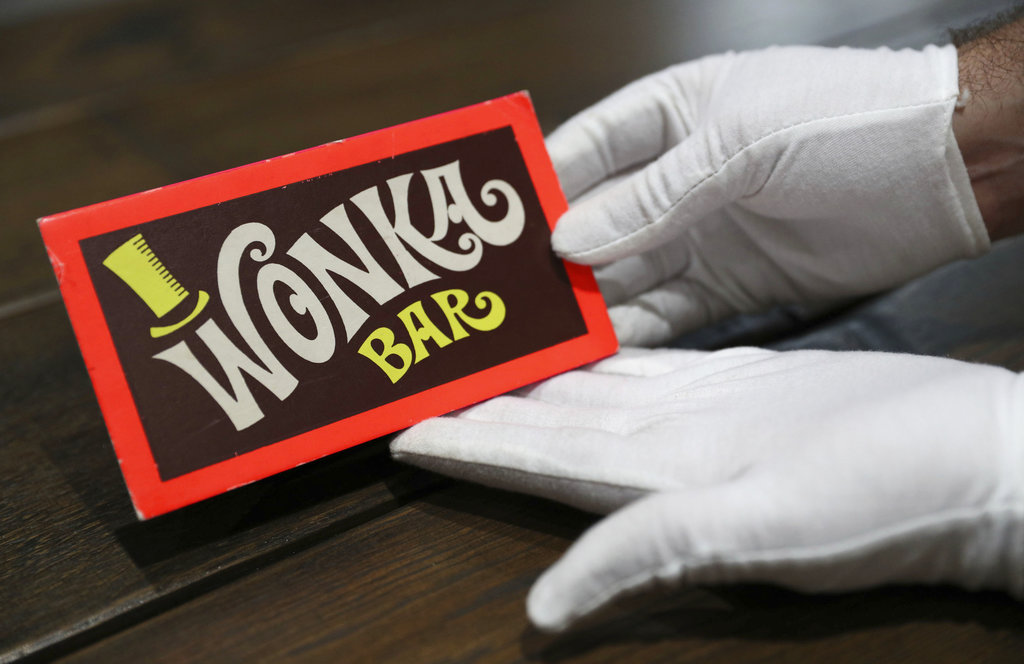 A Prop Store employee holds a Wonka Bar from the film Willy Wonka & the Chocolate Factory on display in the Prop Store head office near Rickmansworth, Enlgnad in 2018. (Andrew Matthews/PA via AP)