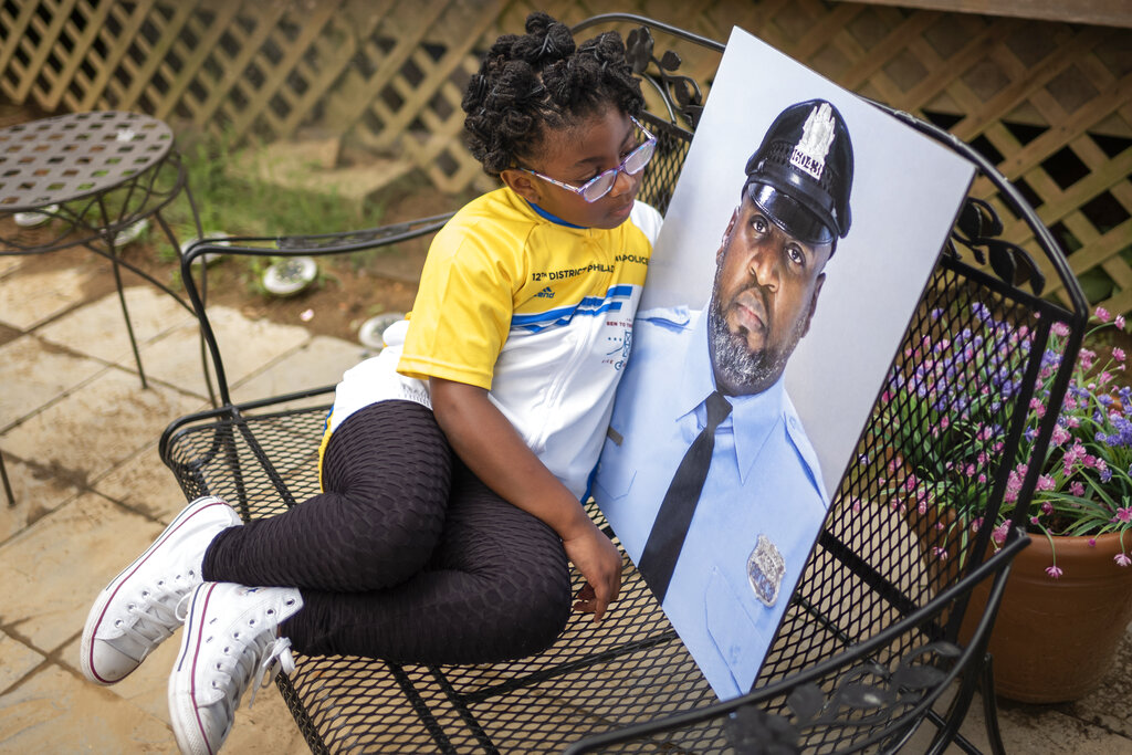 """Amethyst, the five-year old daughter of Erin """"Toke"""" Tokley, a Philadelphia cop who died from COVID-19 in March, poses with a portrait of her father in Secane, Pa. Tokley was scheduled to be vaccinated on March 11 – which turned out to be his funeral. (AP Photo/Laurence Kesterson)"""
