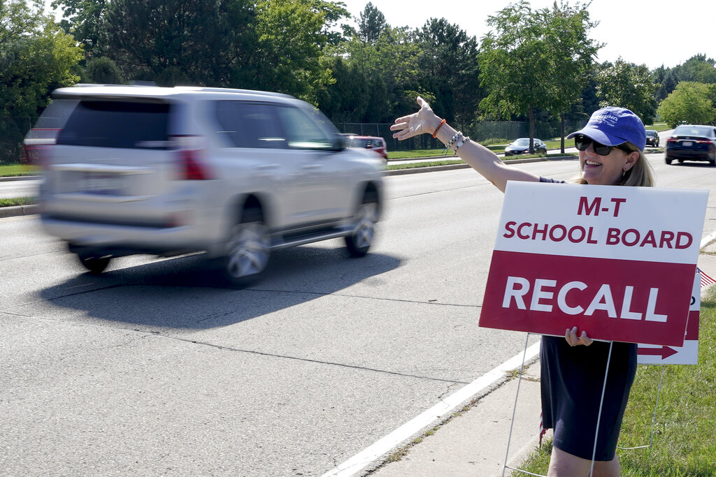 Maureen Hall, a supporter of recalling the entire Mequon-Thiensville School District board, waves at drivers outside Homestead High School Monday, Aug. 23, 2021, in Mequon, Wis. A loose network of conservative groups with ties to major Republican donors and party-aligned think tanks is quietly lending firepower to local activists engaged in the culture war fights in schools across the country. (AP Photo/Morry Gash)