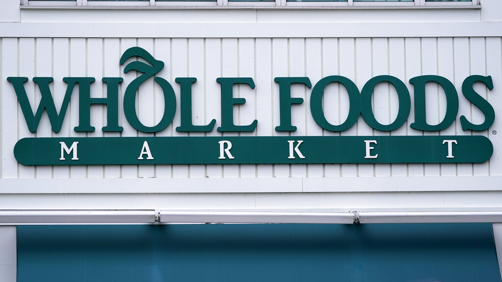 The Whole Foods Market logo is shown on the front of a store in Cambridge, Mass. Amazon, which owns the grocery chain, said Wednesday, Sept. 8, that it will bring its cashier-less technology to two Whole Foods stores for the first time, letting shoppers grab what they need and leave without having to open their wallets. (AP Photo/Charles Krupa)