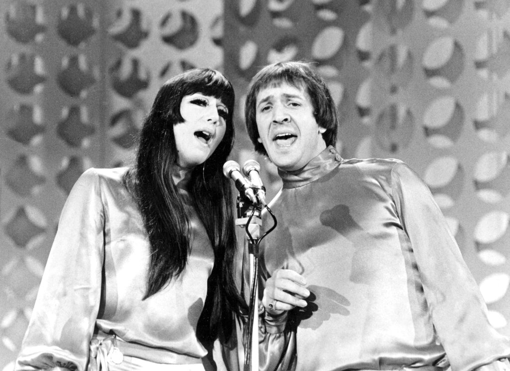 """In this Jan. 21, 1966 file photo, Sonny, right, and Cher sing during a taping of """"The Danny Thomas Special"""" in Los Angeles. Cher has sued the widow of her former musical partner and ex-husband Sonny Bono over royalties for Sonny and Cher songs including """"I Got You Babe"""" and """"The Beat Goes On."""" In a federal lawsuit filed Wednesday, Oct. 13, 2021, Cher alleges that former Rep. Mary Bono and other defendants have attempted to terminate provisions of business agreements Cher and Sonny Bono reached when they divorced in 1975 that entitled each to 50% of songwriting and recording royalties. (AP Photo/File)"""