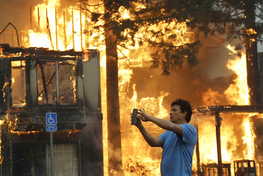 Rudy Habibe, from Puerto Rico, stands by the burning Hilton Sonoma Wine Country hotel, where he was a guest, in Santa Rosa, Calif., Monday, Oct. 9, 2017. Wildfires whipped by powerful winds swept through Northern California, sending residents on a...