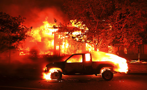 Coffey Park homes burn early Monday Oct. 9, 2017 in Santa Rosa, Calif. More than a dozen wildfires whipped by powerful winds been burning though California wine country. The flames have destroyed at least 1,500 homes and businesses and sent...
